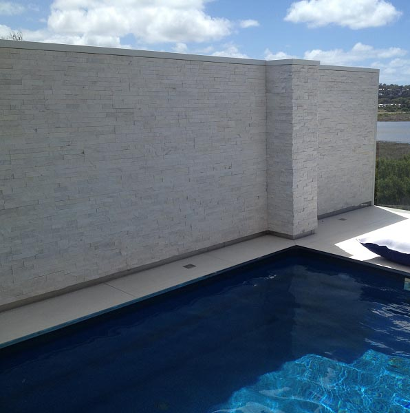 muro de borde de piscina revestida con cuarzo blanco