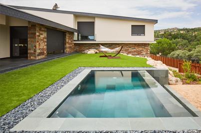 Vista exterior de jardines y piscina revestida con pizarra gris verde